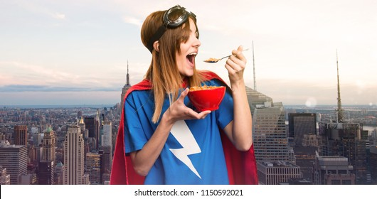 Pretty superhero girl eating cereals from a bowl in a skyscraper city