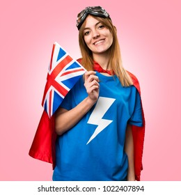 Pretty superhero girl holding an United Kingdom flag on colorful background