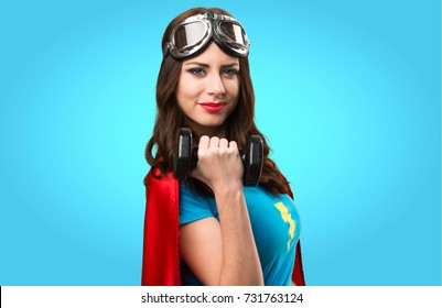Pretty superhero girl making weightlifting on colorful background