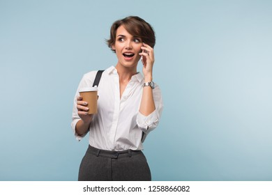 Pretty surprised girl with dark short hair in white shirt holding cup of coffee to go in hand amazedly looking aside talking on cellphone over blue background