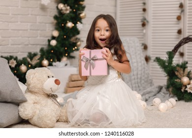 Pretty surprised happy girl holding Christmas gift in hand at home