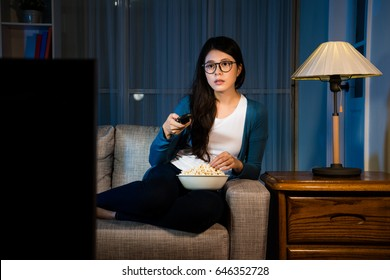 pretty sweet female student holding remote control looking at television and eating delicious popcorn snack at night in living room comfortable sofa.