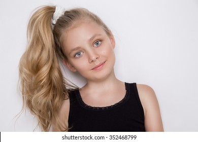 Pretty sweet girl with blond hair in a ponytail with long hair in a child sportswear looks at the camera