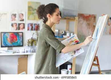 Pretty talented female painter painting on easel, making colorful sketches, creating marine landscape. Beautiful female artist painting with watercolor paints. Creativity and imagination concept