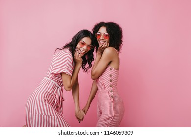 Pretty tanned girls joking during photoshoot on pink background. Indoor photo of refined female models with black hair.