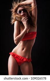 Pretty tanned woman in bikini on black background.