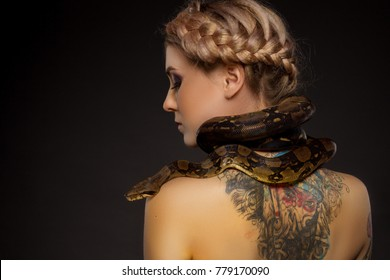 Pretty tattooed blonde with python rearview
