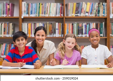 Pretty teacher helping pupils in library at the elementary school