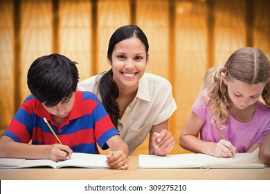 Pretty teacher helping pupils in library against window overlooking city