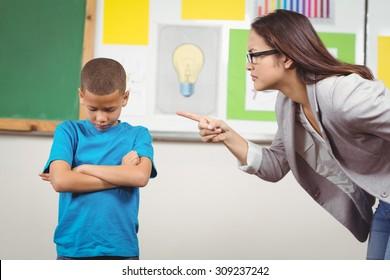 Pretty teacher reprimanding a pupil in a classroom