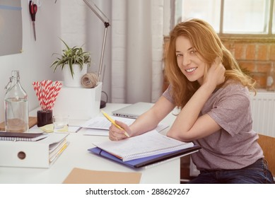 Pretty Teen Blond Girl Smiling at the Camera While Writing Something at her Personal Study Area.