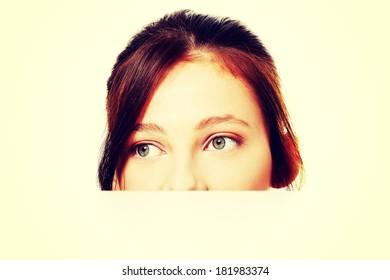Pretty teen brunette student hiding behind sheet of paper.