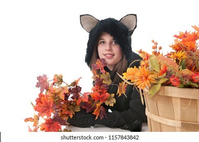 A pretty teen girl in a cat costume laying among colorful fall leaves and flowers.
