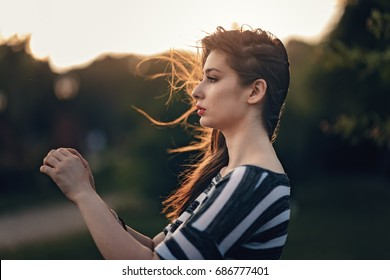 Pretty teen girl having pierced ear without earring. Girl standing in sunlight enjoying breeze. Hands kept ahead face. Long lazy hair shining in evening sunlight and fluttering in breeze.