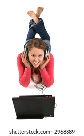 Pretty teen girl with headphones and laptop listening to the music