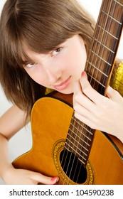 Pretty teen girl playing guitar