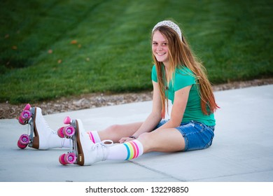 Pretty teen girl in roller skates smiling as she sits on the sidewalk