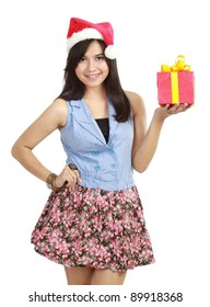 Pretty teen girl in Santa hat presenting gift isolated on white