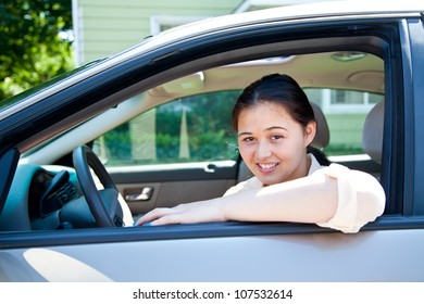 A pretty teen girl sitting in the driver's seat of a car.