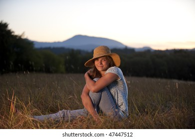 Pretty teen girl sitting in a field in the evening light
