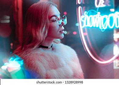 Pretty teen girl in stylish glasses and fur standing near blue pink neon light sign on street, fashion trendy teenager hipster young woman retrowave synthwave style, modern glow night city background