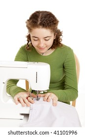 Pretty teen girl using a sewing machine.  Isolated on white.