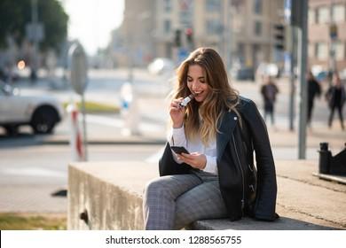 Pretty teen woman sitting on concrete slab at roadside