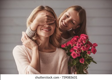 Pretty teenage daughter is holding flowers and covering her mom's eyes while making a surprise, both are smiling