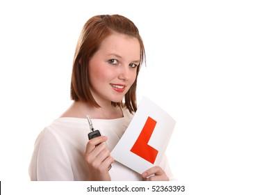 Pretty teenage driver holding L-plates and car key.