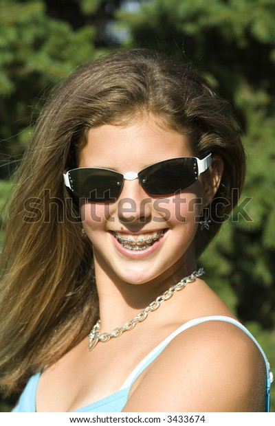 Pretty teenage girl with braces smiling outdoors wearing sunglasses.