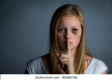 Pretty teenage girl with bruising holding finger to mouth