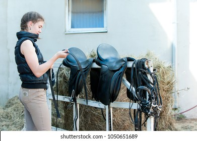 Pretty teenage girl equestrian cleans black Leather Horse Saddle and equipment at farm on bright sunny day. Horizontal outdoors summertime image.