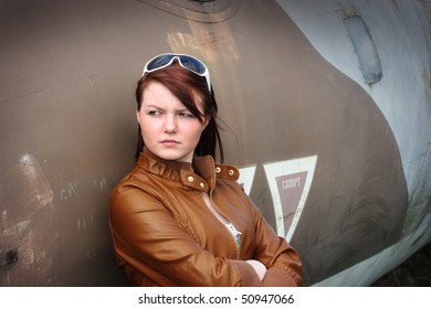 Pretty teenage girl leaning against disused military aircraft