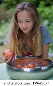 Pretty teenage girl with long blond hair choosing a fresh red apple form a bowl of freshly harvested fruit on a garden table for a tasty healthy summer snack