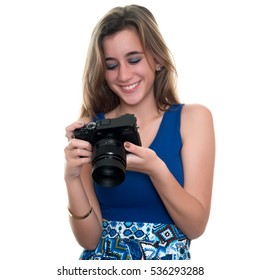 Pretty teenage girl looking at pictures on the rear display of a professional camera  - Isolated on a white background