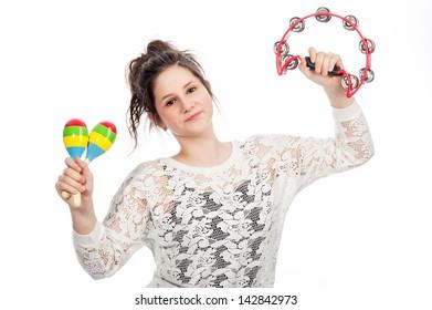 Pretty teenage girl shaking tambourine and maracas in studio on white background.
