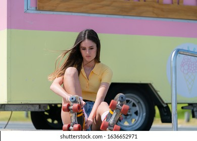 Pretty teenage girl sits on pavement changing shoes for retro old pair roller skates with red laces beside retro caravan