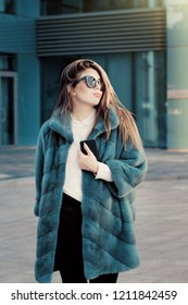 Pretty teenage girl wearing white shirt, bright colorful natural fur coat and sunglasses walking on the street with a smart phone in her hand