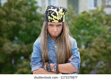 Pretty teenage woman in bandana looking offended and upset at camera pursing lips