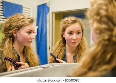 pretty teenager combing her hair in front of a mirror