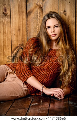 19616931ab40 Pretty teenager girl in casual clothes sitting by a wooden wall. Modern teen  generation. Youth fashion. Healthy hair