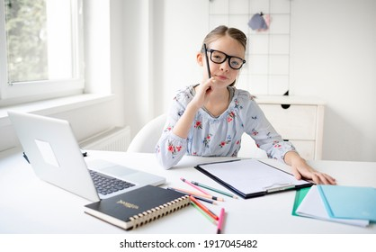 Pretty teenager girl doing homework sitting behind the table at home. Young beautiful girl with glasses, learning online with a laptop, distance learning, self-education