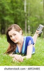 pretty teenager lying down on green grass in blue dress