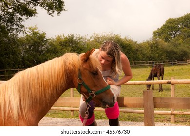 Pretty teenager sits on the fence stroking her horse.