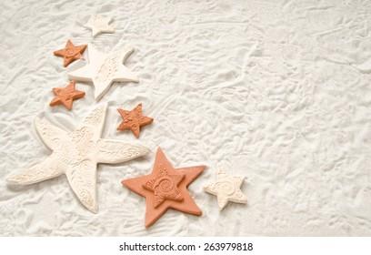 Pretty terra cotta and porcelain stars on a white sand background