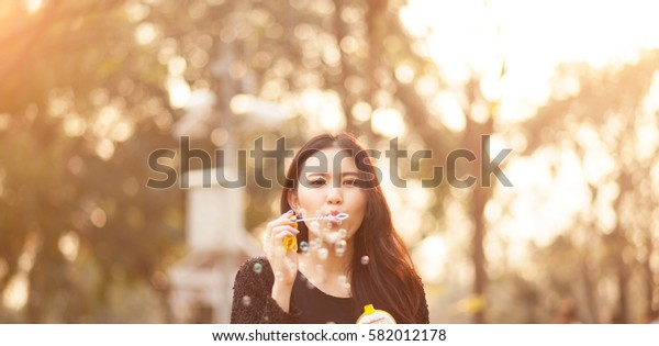 Pretty Thai girl blowing a bubbles at the park