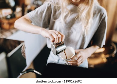 A pretty thin blonde girl with long hair, dressed in casual outfit, pours coffee into a glass in a cozy coffee shop.