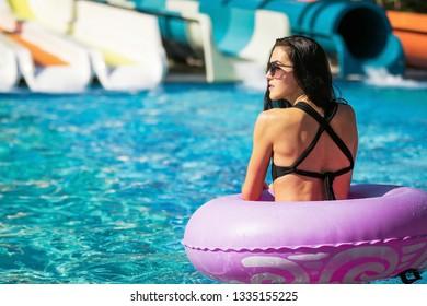 pretty thoughtful woman with slim figure in black bikini a swim ring in the swimming pool. Summer Vacation. Enjoying suntan. Weekend on resort