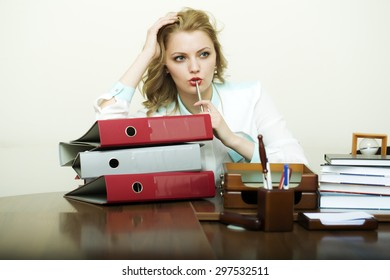 Pretty thoughtful working business woman sitting in office at table with many documents books files folders has a lot of work holding pen on white background, horizontal picture