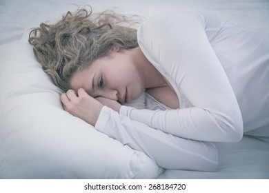 Pretty tired girl lying in bed with sad thoughts